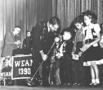 Master of Ceremonies Lt Palmer speaks to fans gathered at the Glebe Theater during a WEAM-AM radio remote. (From the family archives of Helen A. Palmer)